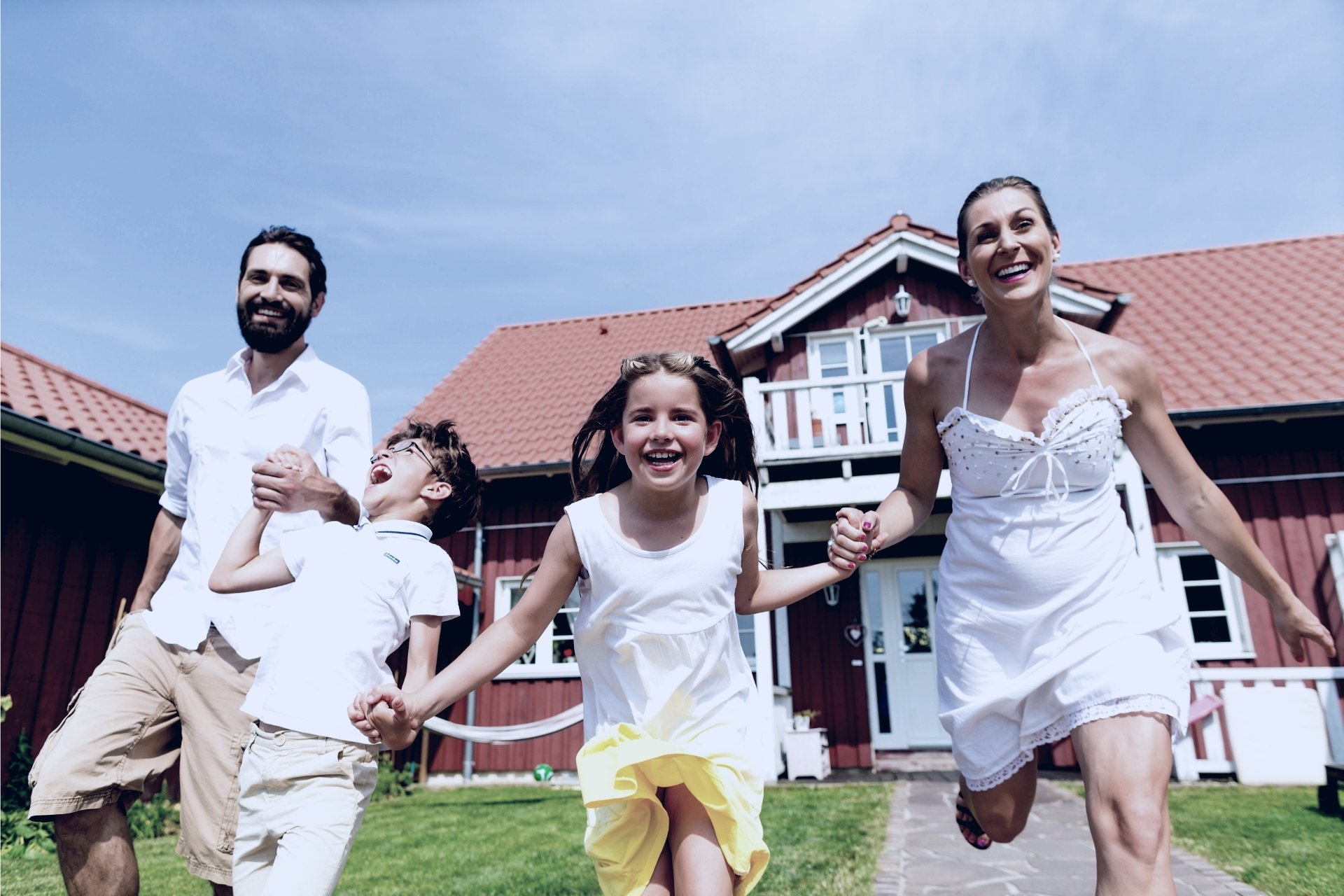First-time home buyer family in white jumping in front of house