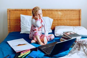 Girl nodding off with books and laptop