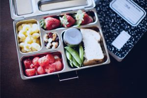 Healthy lunch box with fruits and a notebook