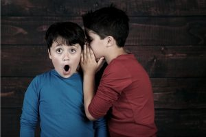 Boy with shocked face as other boy whispers in ear
