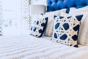 Matching blue and white pillows on bed for staging a home