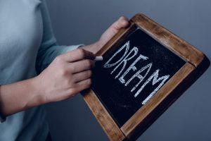 Writing DREAM on handheld blackboard | Raboin Realty
