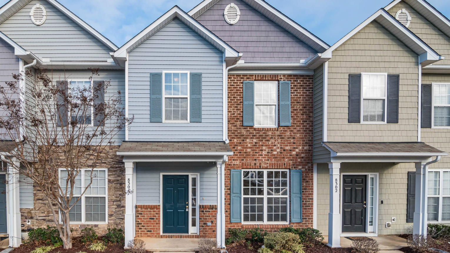 Townhouse with blue siding and brick accent.