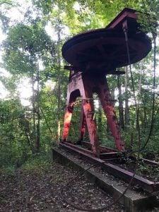 Rusted red ski lift abandoned in historic Mill Ridge neighborhood.