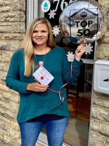 Sarah Long holding a Top 50 Brokers of the High Country of North Carolina Balloon at the 828 Real Estate office.