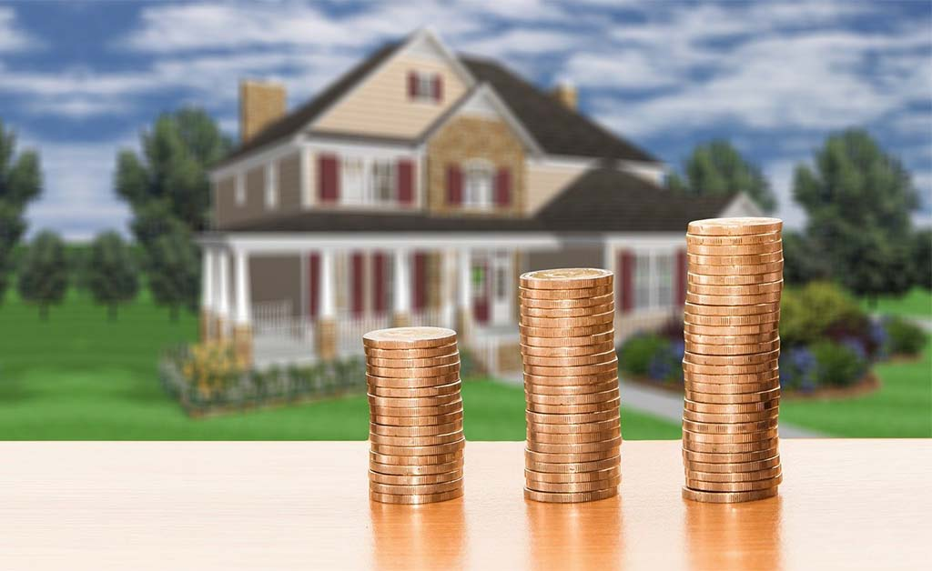 Saving for a mortgage downpayment as a renter. pennies stacked in front of a beautiful home.