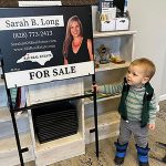Toddler looking at a for sale sign from 828 Real Estate's Sarah Long.