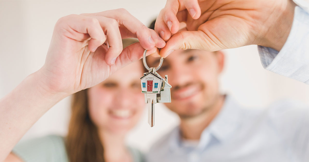 Man and woman holding keys to their new home.