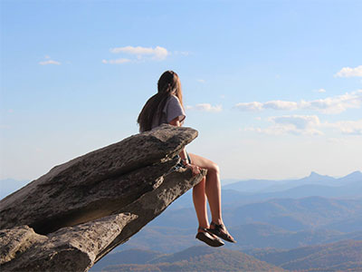 Girl sitting on the edge of the cliff at Rough Ridge in Boone, NC.