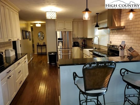 White kitchen with stainless steel appliances inside kitchen in a home for sale in Boone, NC