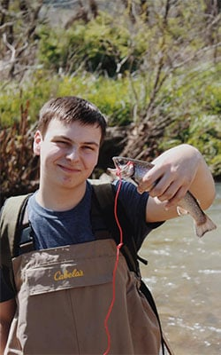 Man holding a fish in a stream in Valle Crucis, North Carolina.