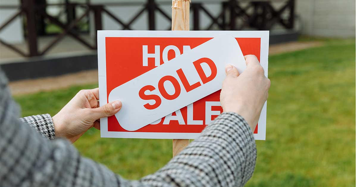 Realtor placing a sold sticker on a sign for a home that sold during a real estate bidding war in Boone, NC