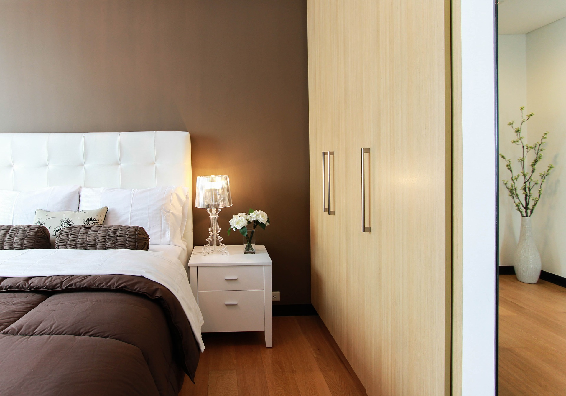 Bedroom with brown bedding and sleek modern closets.