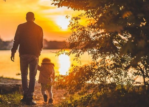 dad and child by the lake at sunset