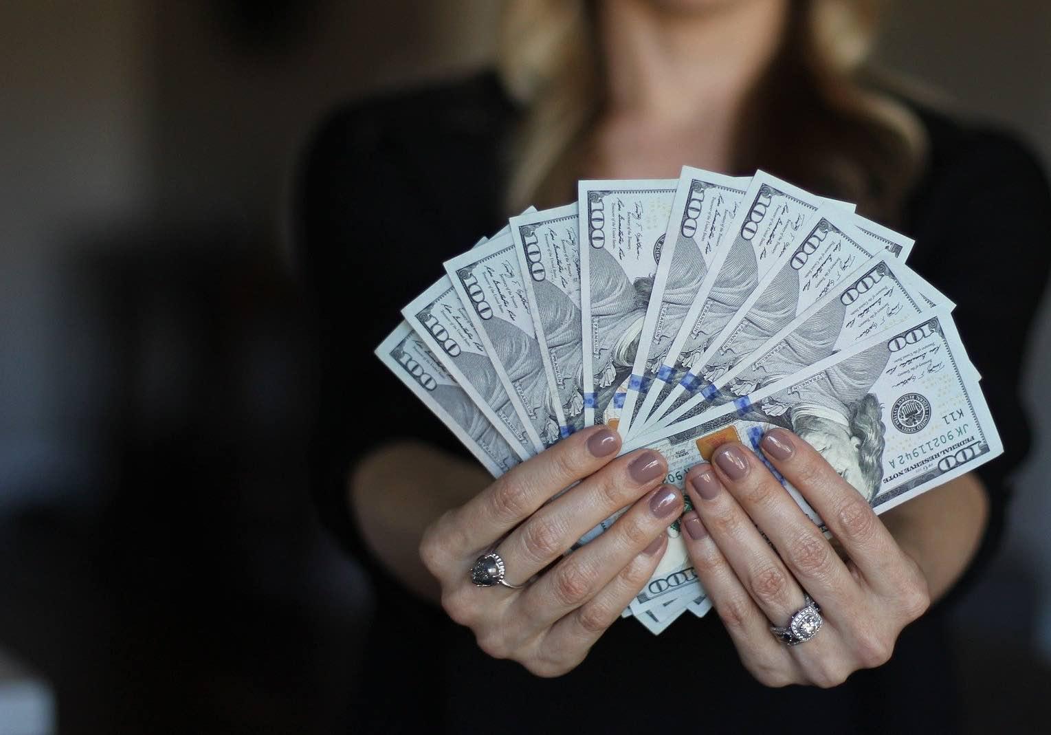 Woman holding one-hundred dollar bills, money for earnest money.