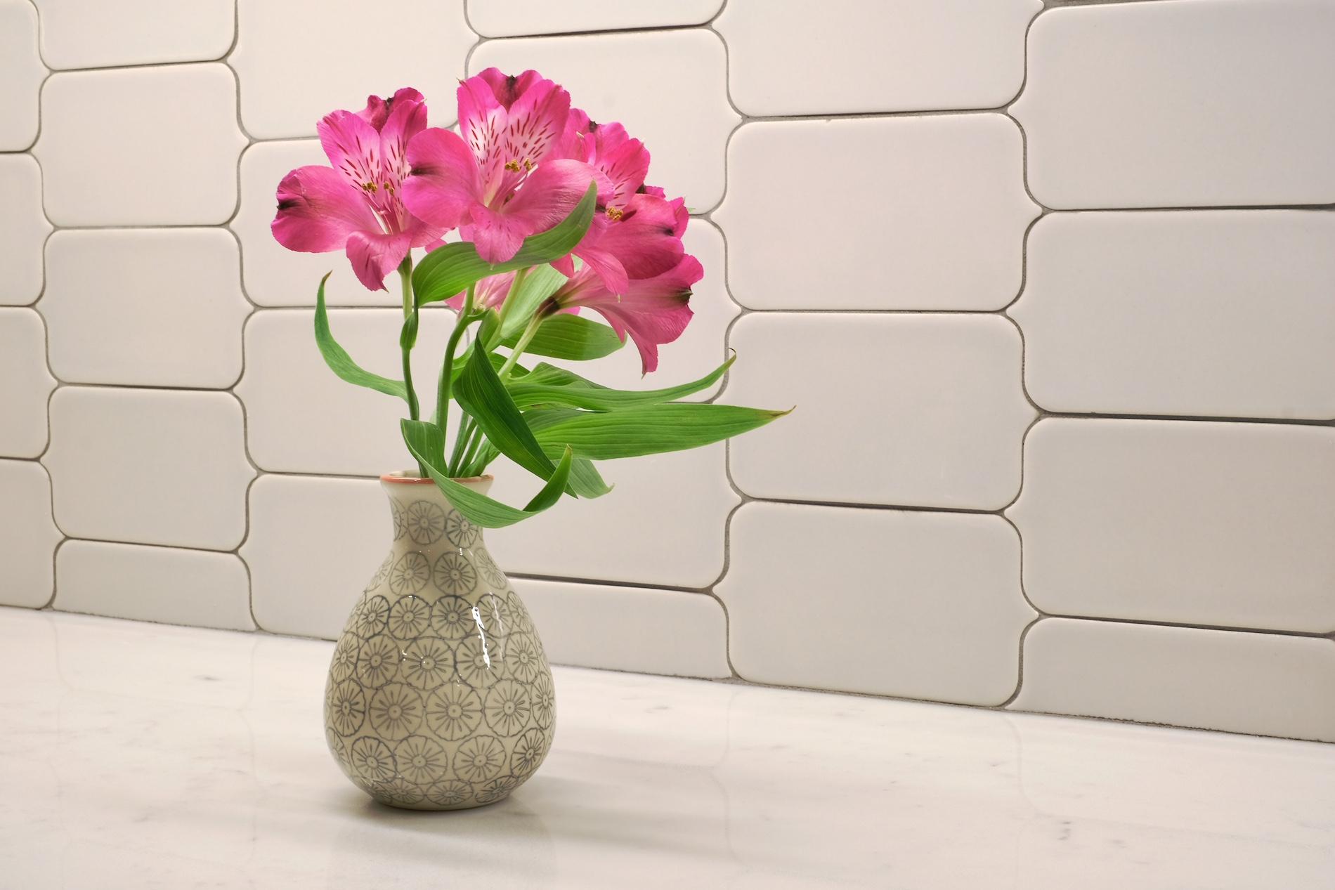 handmade paddle tile backsplash, white quartz counter tops, flowers
