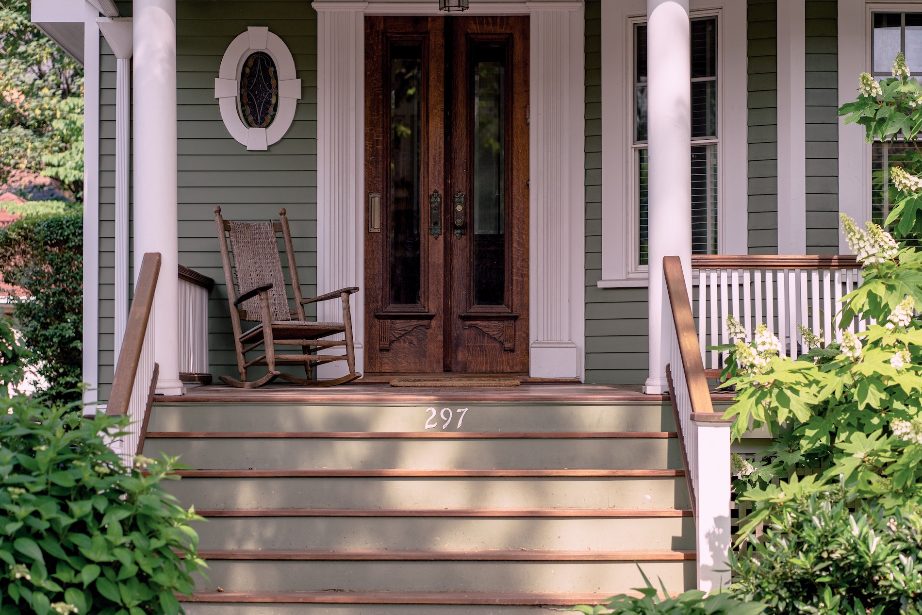 Beautiful front porch, white pillars, painted stairs, antique wood glass doors