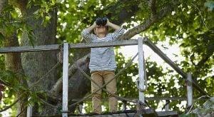 Boy using binoculars on treehouse