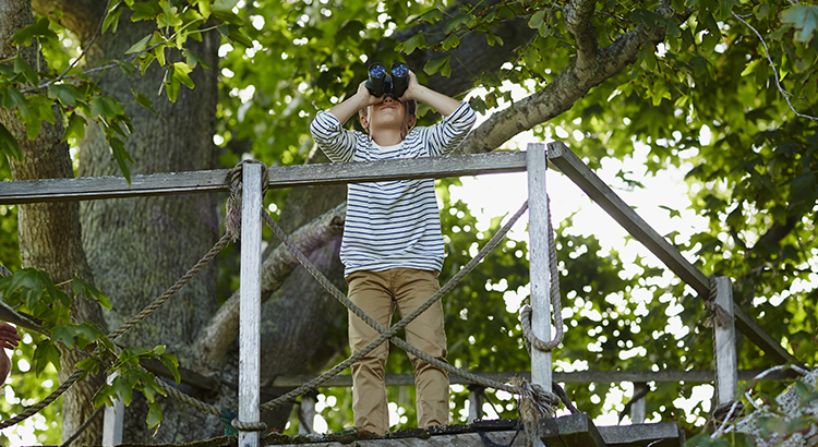 Boy using binoculars on treehouse