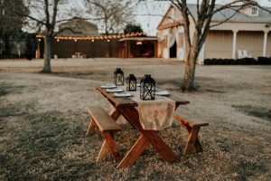 picnic table decorated for outdoor gathering with string lights